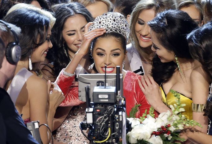 Miss USA Olivia Culpo (center) smiles for the television camera as she is congratulated by other contestants after being crowned Miss Universe on Wednesday, Dec. 19, 2012, in Las Vegas. (AP Photo/Julie Jacobson)