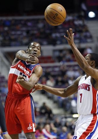 Washington Wizards guard Jordan Crawford (15) passes the ball against Detroit Pistons guard Brandon Knight (7) in the first half of an NBA basketball game in Auburn Hills, Mich., Friday, Dec. 21, 2012. (AP Photo/Duane Burleson)