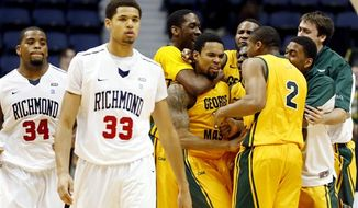 """George Mason""""s Sherrod Wright (C) is mobbed by teammates after hitting a three-pointer at the buzzer to lead George Mason to a 67-64 victory in an NCAA college basketball game in the 2012 Governor's Holiday Hoops Classic at The Richmond Coliseum in Richmond, VA.,Saturday, Dec.,22,2012. At left dejected Richmond players are Derrick Williams (34) and Alonzo Nelson-Ododa (33). (AP Photo/The Richmond Times-Dispatch, Joe Mahoney)"""