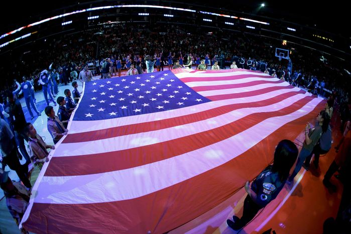 Local scout troops display a large American flag during the National Anthem before NBA basketball game between the Los Angeles Clippers and the Sacramento Kings in Los Angeles, Friday, Dec. 21, 2012. (AP Photo/Chris Carlson)