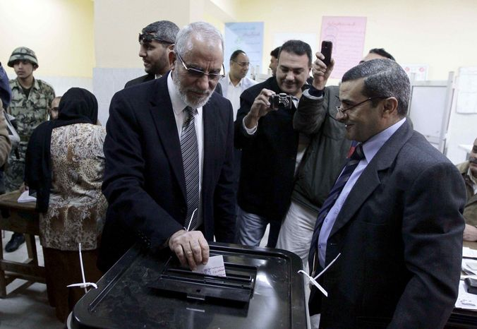 Muslim Brotherhood leader Mohammed Badie, second right, waits in line outside a polling place in Beni Suef, Egypt, to vote on a constitution drafted by Islamist supporters of President Mohammed Morsi, Saturday, Dec. 22, 2012. (AP Photo/Mohamed Nohan, El Shorouk Newspaper)