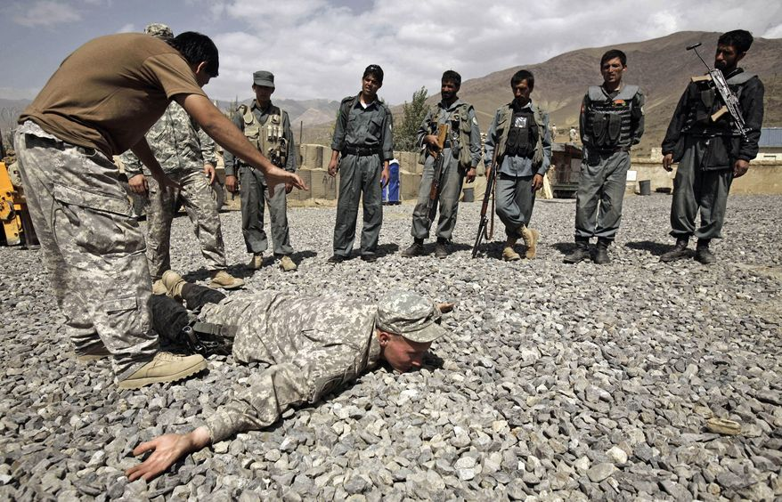 ** FILE ** U.S. Army Sgt. William Womack, 23, of Batesville, Ga., of the 118th Military Police Company, based at Fort Bragg, N.C., is prone during a training session for the Afghan National Police at a combat outpost in the Jalrez Valley in Afghanistan's Wardak Province in 2009. (AP Photo/Maya Alleruzzo)