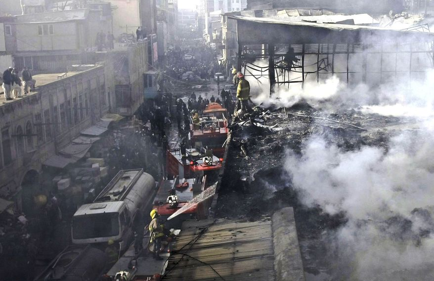 Policemen and firefighters investigate the scene of a burning market in Kabul, Afghanistan, on Sunday, Dec. 23, 2012. Hundreds of shops at a market were damaged in the blaze, but no causalities were reported. (AP Photo/Musadeq Sadeq)