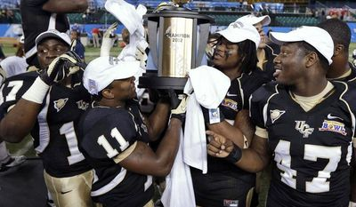 Central Florida players, from left, Cedric Thompson, Jonathan Davis, E.J. Dunston, and Deion Green celebrate with the trophy after Central Florida defeated Ball State 38-17 during the Beef 'O' Brady's Bowl NCAA college football game Friday, Dec. 21, 2012, in St Petersburg, Fla. (AP Photo/Chris O'Meara)