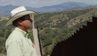 Dan Bell, who owns a 35,000-acre cattle ranch along the border between the United States and Mexico, looks at the imposing border fence near Nogales, Ariz., on Friday, Aug. 10, 2012. (AP Photo/Ross D. Franklin)