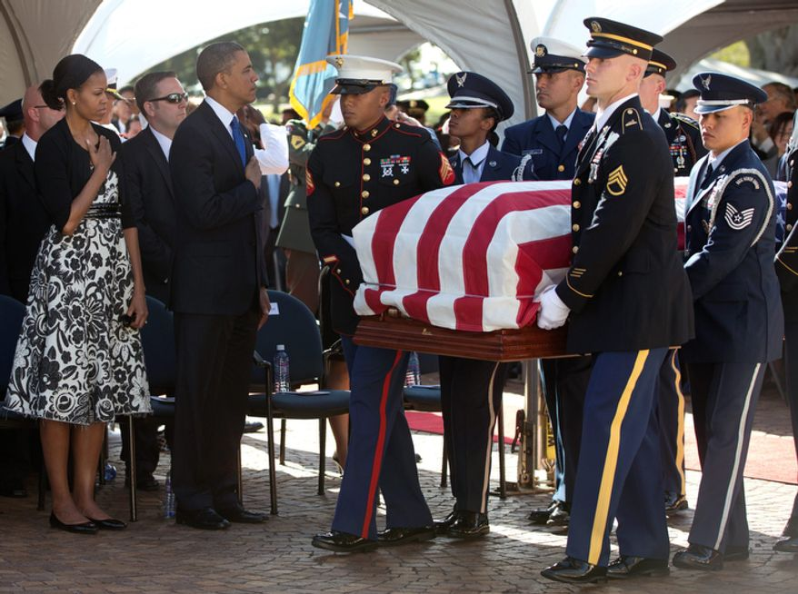 President Barack Obama and First Lady Michelle Obama stand with their hands over their hearts as the flag-draped casket of the late Sen. Daniel Inouye, D-Hawaii, is carried past during a memorial service at the National Memorial Cemetery of the Pacific, Sunday, Dec. 23, 2012, in Honolulu. (AP Photo/Carolyn Kaster)