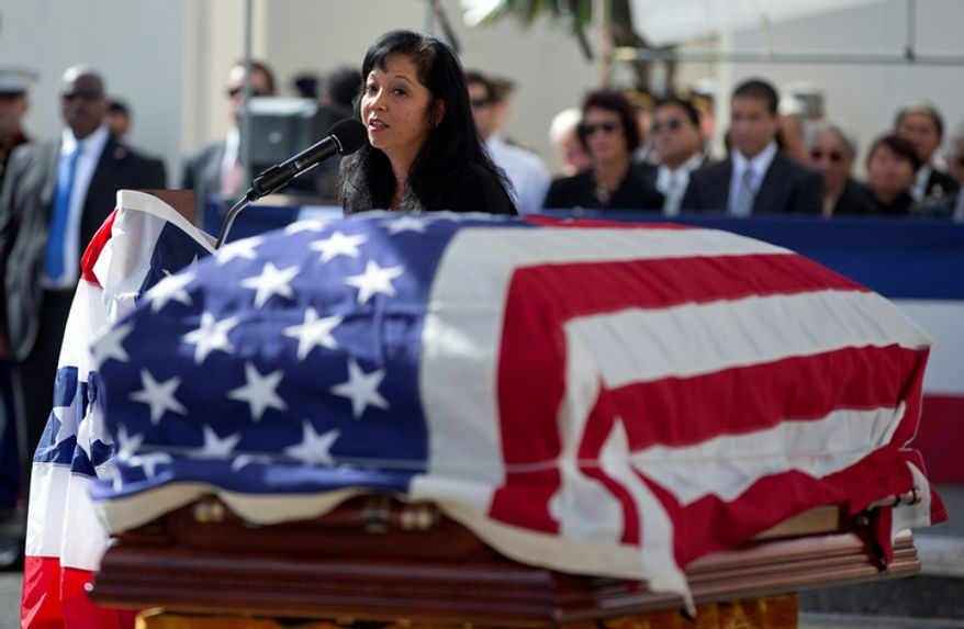 Jennifer Sabas, chief of staff for the late Sen. Daniel Inouye, D-Hawaii, looks toward his flag-draped casket during a memorial service at the National Memorial Cemetery of the Pacific, Sunday, Dec. 23, 2012, in Honolulu. Inouye, 88, was the first Japanese-American elected to both houses of Congress and the second-longest serving senator in U.S. history. He died Dec. 17. (AP Photo/Carolyn Kaster)