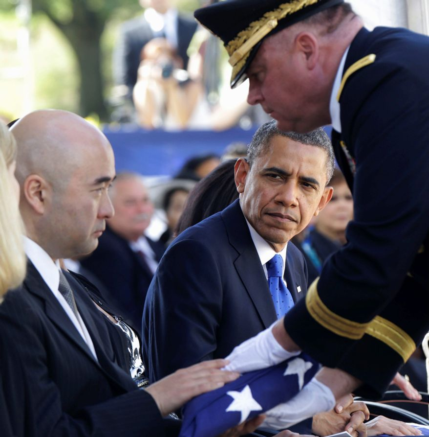 President Obama watches as Lt. Gen. Francis Wiercinski, commander of the U.S. Army Pacific, presents an American flag to Daniel Inouye, Jr., son of Sen. Daniel Inouye, D-Hawaii, during the memorial service for the late senator at National Memorial Cemetery of the Pacific in Honolulu, Sunday, Dec. 23, 2012. (AP Photo/Gerald Herbert)