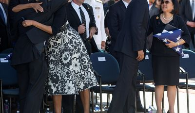 President Barack Obama, center right, comforts Irene Hirano Inouye, visits with the widow of the late Sen. Daniel Inouye, right, as first lady Michelle Obama embraces Inouey's son, Daniel Ken Inouye, Jr., left,  during a memorial service for the late senator at the National Memorial Cemetery of the Pacific, Sunday, Dec. 23, 2012, in Honolulu. Inouye, D-Hawaii, was the first Japanese-American elected to both houses of Congress and the second-longest serving senator in U.S. history. He died Dec. 17 at the age of 88. (AP Photo/Carolyn Kaster)