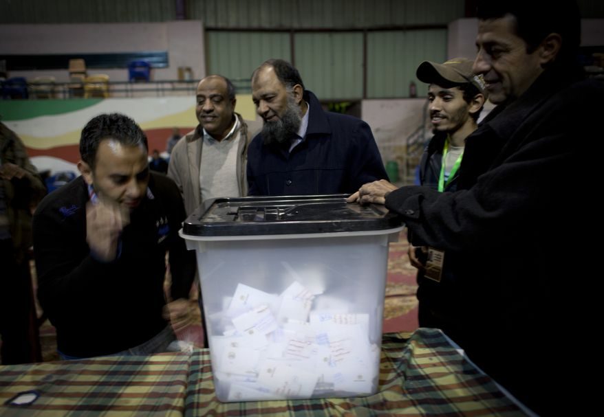 Election workers unseal a ballot box for counting at the end of the second round of a referendum on a disputed Egyptian constitution drafted by Islamist supporters of President Mohammed Morsi at a polling station in Giza, Egypt, on Saturday, Dec. 22, 2012. (AP Photo/Nasser Nasser)