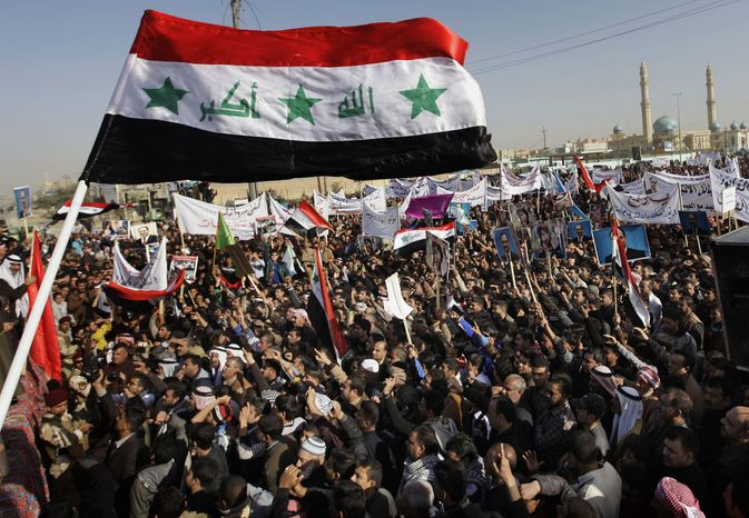 ** FILE ** Protesters chant slogans against Iraq's Shiite-led government as they wave national flags and hold posters of Sunni Finance Minister Rafia al-Issawi during a demonstration in Fallujah, 40 miles west of Baghdad, on Sunday, Dec. 23, 2012. Thousands protested in Iraq's western Sunni heartland following the arrest of bodyguards assigned to the finance minister, who draws support from the area. The Khulafa al-Rashideen Mosque is seen at right. (AP Photo/Khalid Mohammed)
