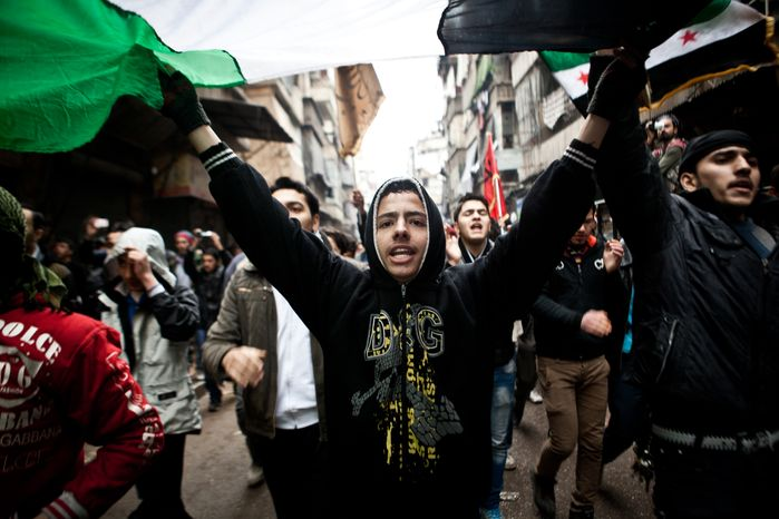 Syrian protesters carry a large revolution flag and chant slogans during a demonstration in Aleppo, Syria, where young people and children sang songs against President Bashar Assad and his regime on Friday, Dec. 21, 2012. (AP Photo/Virginie Nguyen Hoang)