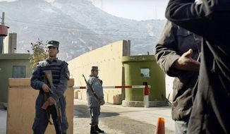 Afghan police stand guard at Kabul police headquarters, where a U.S. civilian adviser was killed by an Afghan policewoman who shot him once in the chest. (Associated Press)
