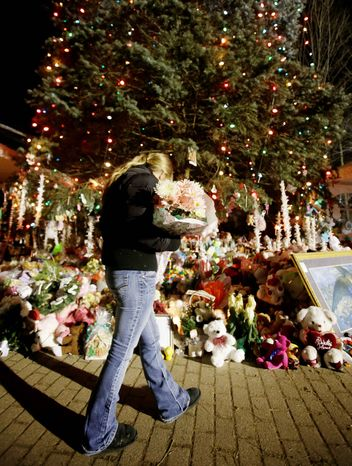 A woman carries flowers to a Christmas tree that has become a memorial to the shooting victims in Newtown, Conn. Sympathetic messages to the community have come from around the world. (Associated Press)