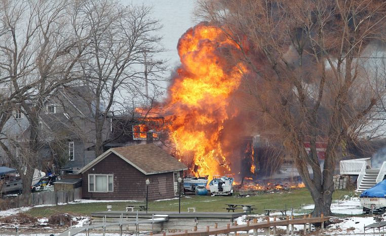 A house burns Monday in Webster, N.Y., a suburb of Rochester on Lake Ontario. A 62-year-old ex-convict set a car and a house ablaze in the neighborhood to lure firefighters before opening fire on them, slaying two. (Associated Press)