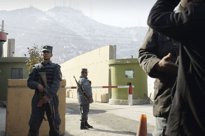Afghan police stand guard outside police headquarters in Kabul, Afghanistan, where an American adviser was killed, authorities said, by an Afghan policewoman on Monday, Dec. 24, 2012. (AP Photo/Musadeq Sadeq)