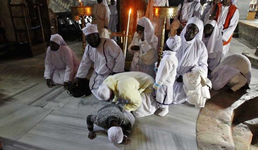 Christian worshippers from Nigeria pray at the Church of Nativity, traditionally believed by Christians to be the birthplace of Jesus Christ, in the West Bank town of Bethlehem, Monday, Dec. 24, 2012.  (AP Photo/Adel Hana)