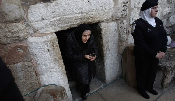 A Christian worshiper walks out of the Church of Nativity, traditionally believed by Christians to be the birthplace of Jesus Christ, in the West Bank town of Bethlehem. (AP Photo/Adel Hana)