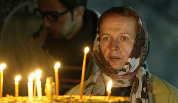 A Catholic pilgrim looks at lit candles outside of the Grotto at the Church of Nativity, traditionally believed by Christians to be the birthplace of Jesus Christ, in the West Bank town of Bethlehem, Monday, Dec. 24, 2012. (AP Photo/Adel Hana)