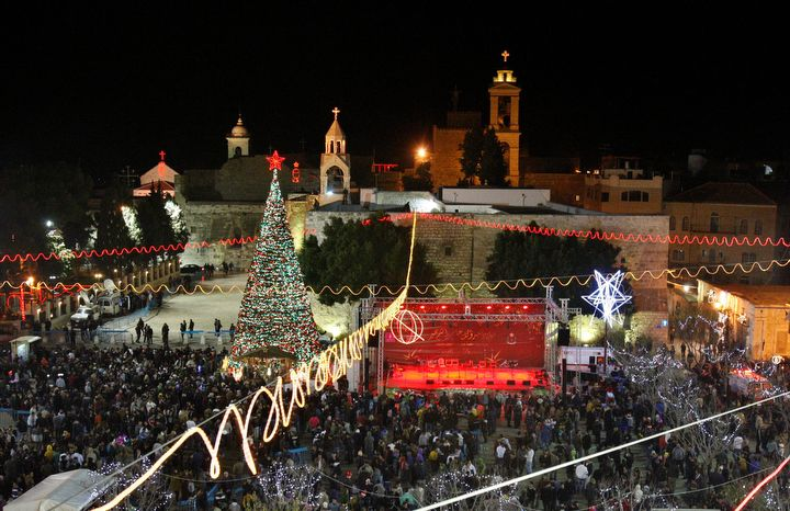Christian worshippers and tourists celebrate at the Manger Square in front of the Church of the Nativity, in the West Bank town of Bethlehem, Monday, Dec. 24, 2012. Thousands of Christian worshippers and tourists arrived in Bethlehem on Monday to mark Christmas at the site where many believe Jesus Christ was born. (AP Photo/Adel Hana)
