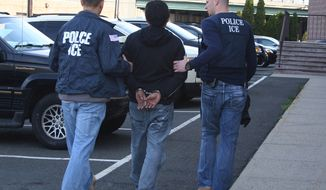 U.S. Immigration and Customs Enforcement agents in New Jersey take a person into custody on March 28, 2012, during Operation Cross Check III. (Associated Press/U.S. Immigration and Customs Enforcement) **FILE**