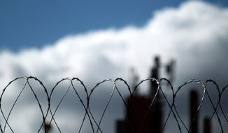 Razor wire sits atop a border fence as a building in the Mexican border city of Tijuana sits behind, as seen from San Diego on Monday, Jan. 31, 2011. (AP Photo/Gregory Bull) ** FILE **
