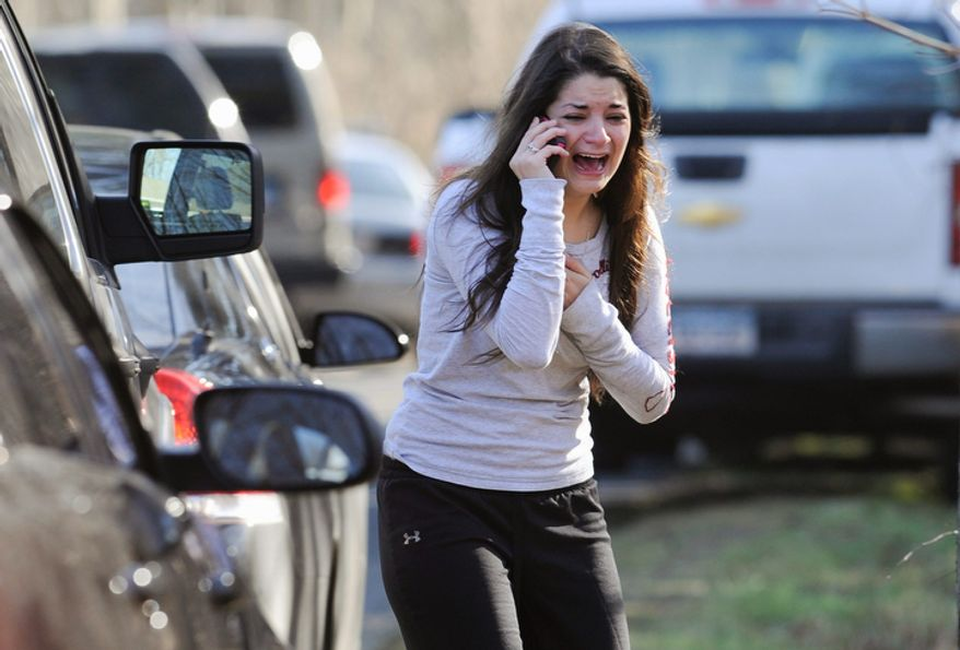 A woman waits to hear about her sister, a teacher, following a shooting at the Sandy Hook Elementary School in Newtown, Conn., about 60 miles northeast of New York, on Friday, Dec. 14, 2012. (AP Photo/Jessica Hill)