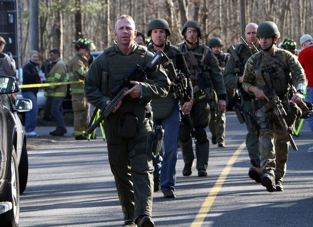 Heavily armed Connecticut state troopers are on the scene at the Sandy Hook Elementary School following the mass shooting on Friday, Dec. 14, 2012, in Newtown, Conn. (AP Photo/The Journal News, Frank Becerra Jr.)