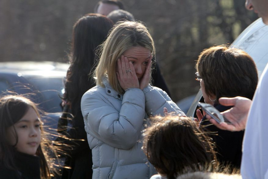 ** FILE ** A woman weeps as she arrives to pick up her children at the Sandy Hook Elementary School on Friday, Dec. 14, 2012, in Newtown, Conn. (AP Photo/The Journal News, Frank Becerra Jr.)