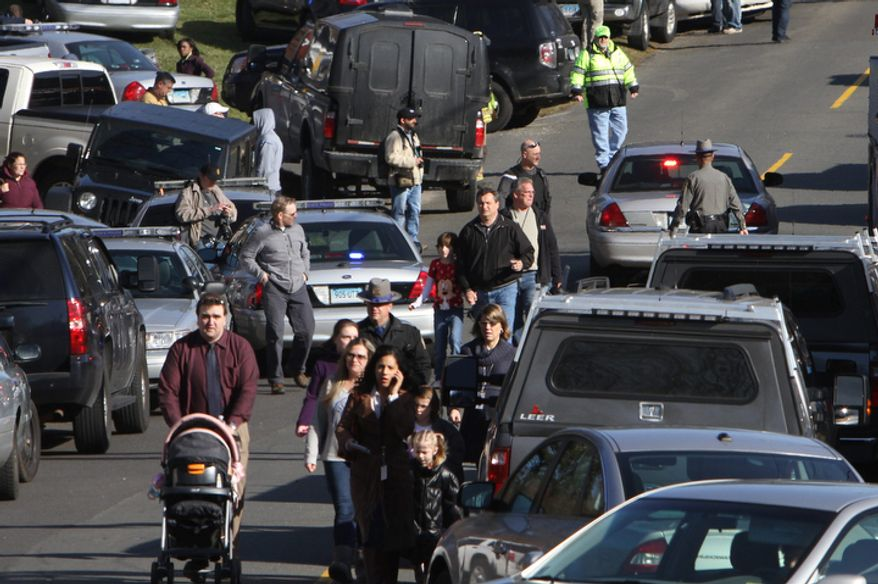 Parents walk away from the Sandy Hook Elementary School with their children following the mass shooting on Friday, Dec. 14, 2012, in Newtown, Conn. (AP Photo/The Journal News, Frank Becerra Jr.)