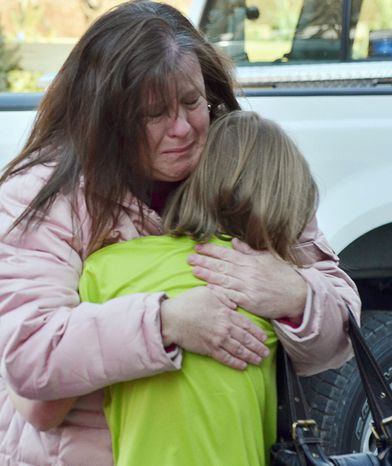 A mother hugs her daughter following a shooting at the Sandy Hook Elementary School in Newtown, Conn., about 60 miles northeast of New York, on Friday, Dec. 14, 2012. (AP Photo/The New Haven Register, Melanie Stengel)