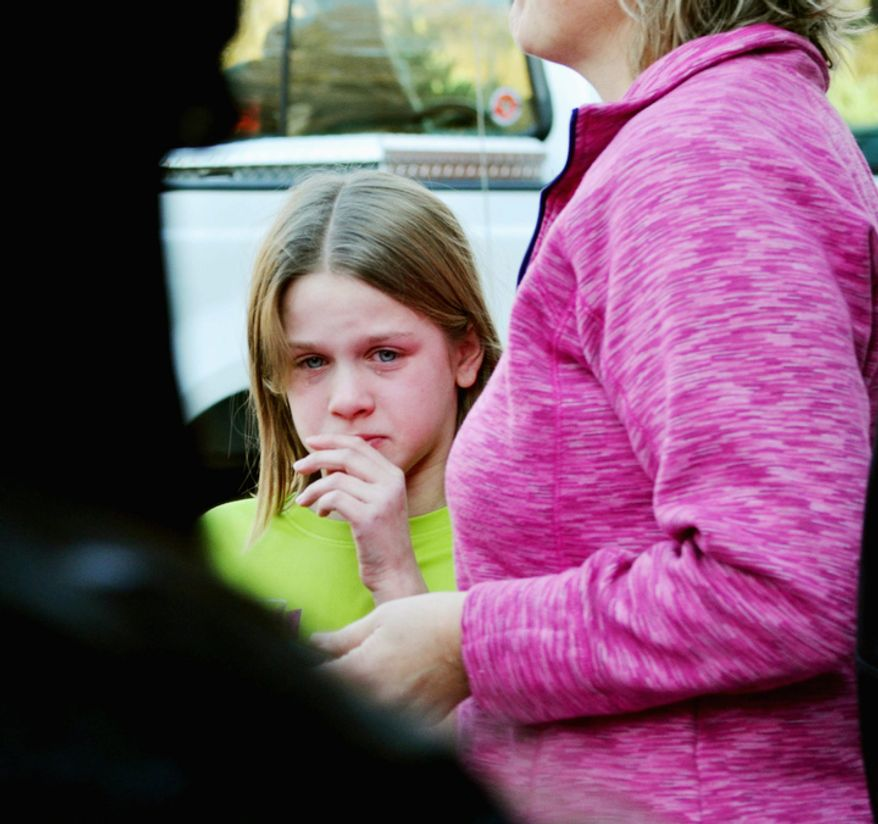 A young girl cries following the mass shooting at the Sandy Hook Elementary School in Newtown, Conn., about 60 miles northeast of New York, on Friday, Dec. 14, 2012. (AP Photo/The New Haven Register, Melanie Stengel)
