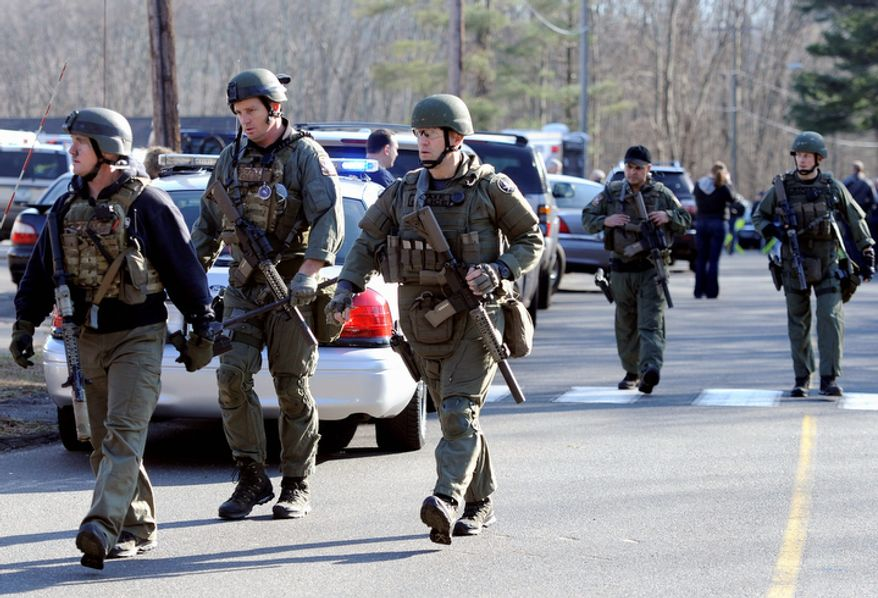 Connecticut State Police are on scene following the mass shooting at the Sandy Hook Elementary School in Newtown, Conn., about 60 miles northeast of New York, on Dec. 14, 2012. (Associated Press) **FILE**