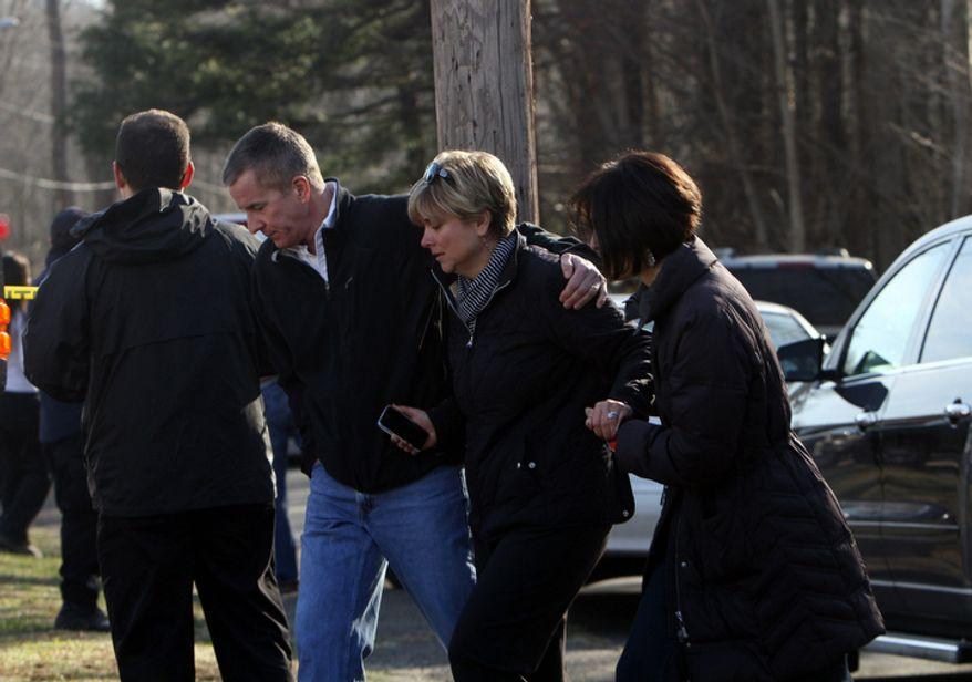Teachers walk away from the Sandy Hook Elementary School following the mass shooting on Friday, Dec. 14, 2012, in Newtown, Conn. (AP Photo/The Journal News, Frank Becerra Jr.)