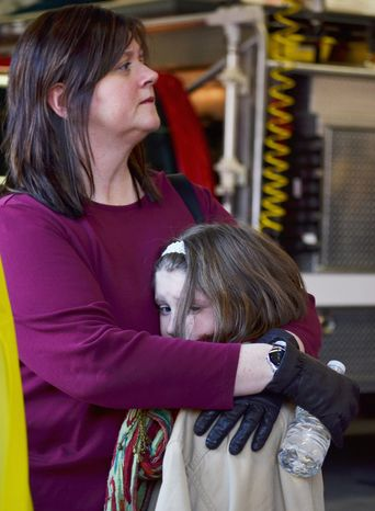 A mother hugs her daughter following the mass shooting at the Sandy Hook Elementary School in Newtown, Conn., about 60 miles northeast of New York, on Friday, Dec. 14, 2012. (AP Photo/The New Haven Register, Melanie Stengel)
