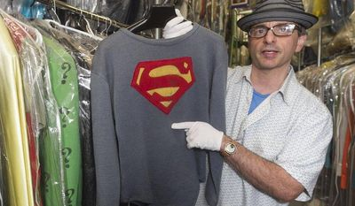 """James Comisar holds the costume George Reeves wore in the 1950s TV show """"The Adventures of Superman,"""" part of Mr. Comisar's television memorabilia collection stored in a temperature- and humidity-controlled warehouse in Los Angeles. (AP Photo/Damian Dovarganes)"""