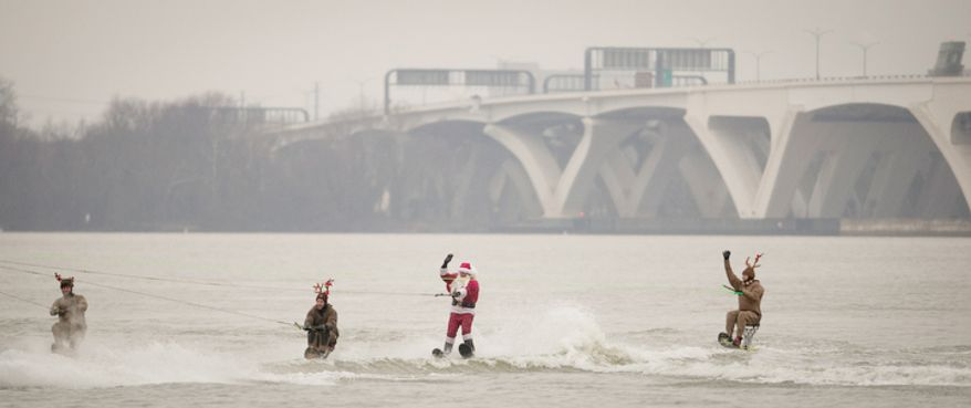 Escorted by reindeer, Santa speeds along the water on his water skis during the 27th annual show of The Water-Skiing Santa on the Potomac River in National Harbor, Md., Monday, Dec. 24, 2012.  (Rod Lamkey Jr./The Washington Times)