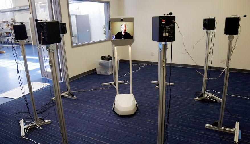 Suitable Technologies Vice President Bo Preising (on screen), tests the Beam remote-presence system in Palo Alto, Calif. With video cameras, microphones and speakers, the remote-controlled machine connects remote workers with colleagues in another location. (Associated Press)