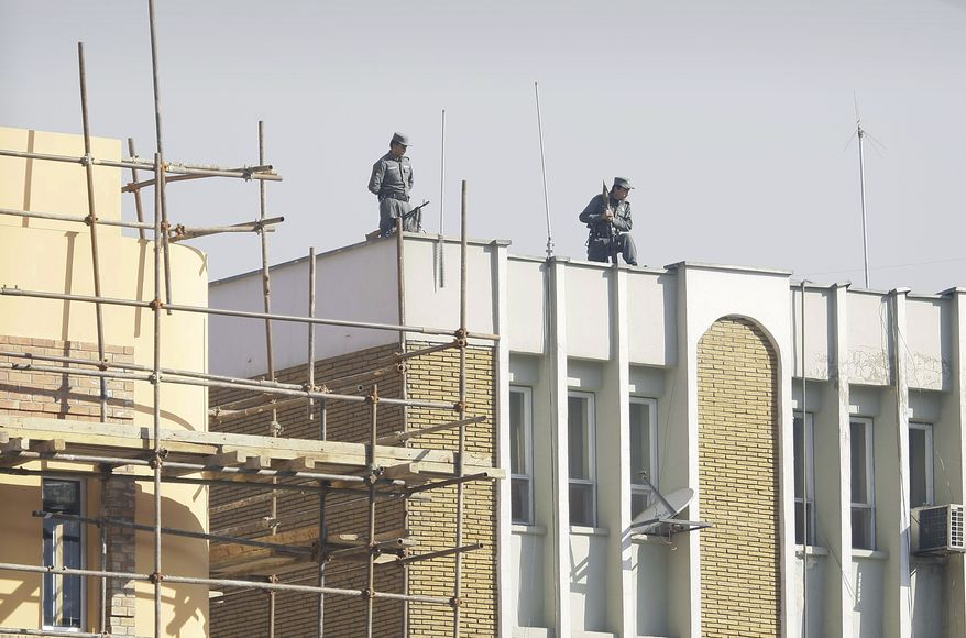 Afghan policemen keep watch from atop city police headquarters in Kabul, Afghanistan, on Monday, Dec. 24, 2012, following the killing of an American adviser by an Afghan policewoman, according to a senior Afghan police official. (AP Photo/Musadeq Sadeq)