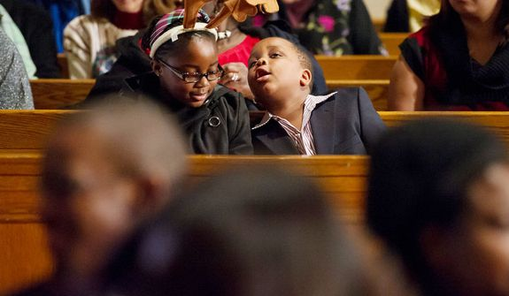 Chidubem Nwabineli, 6, of Bowie, Md., right, checks out the reindeer antlers his sister, Chinemelum, 8, wears as they wait for Archbishop of Washington Cardinal Donald Wuerl to lead a congregation of 4,000 in Solemn Mass of Christmas Day at the Basilica of the National Shrine of the Immaculate Conception, Washington, D.C., Tuesday, December 25, 2012. (Andrew Harnik/The Washington Times)