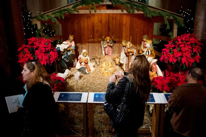 Church attendees get a look at a Christmas manger scene before Archbishop of Washington Cardinal Donald Wuerl leads a congregation of 4,000 in Solemn Mass of Christmas Day at the Basilica of the National Shrine of the Immaculate Conception, Washington, D.C., Tuesday, December 25, 2012. (Andrew Harnik/The Washington Times)