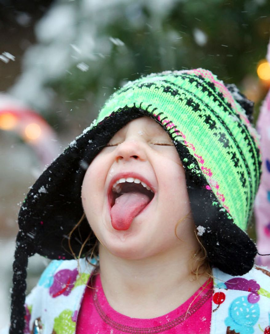 Iris Davis sticks her tongue out trying to catch snowflakes Tuesday, Dec. 25, 2012 after a strong winter system dropped inches of rain and snow on most of North East Texas.  (AP Photo / The Paris News, Sam Craft)