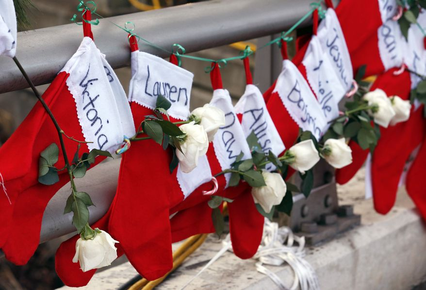 Christmas stockings with the names of the victims of the Sandy Hook Elementary School shooting hang from a railing near a makeshift memorial near the town Christmas tree in the Sandy Hook village of Newtown, Conn., on Wednesday, Dec. 19, 2012. In the wake of the shooting, the grieving town is trying to find meaning in Christmas. (AP Photo/Julio Cortez)