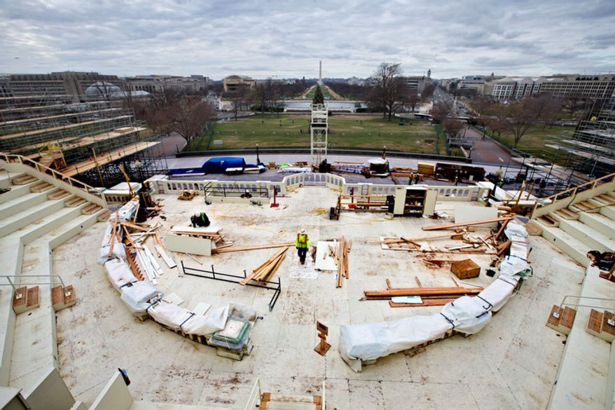 In this Dec. 11, 2012, file photo, construction workers continue work on the platforms on the west side of the Capitol where dignitaries and news cameras will witness the inaugural ceremonies on Capitol Hill in Washington.  (AP Photo/J. Scott Applewhite, File)
