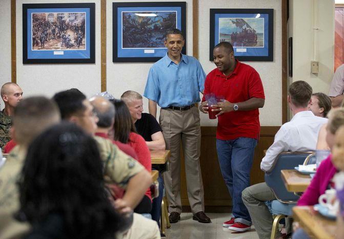President Barack Obama visits with members of the military and their families in Anderson Hall at Marine Corp Base Hawaii, Tuesday, Dec. 25, 2012, in Kaneohe Bay, Hawaii. The first family is in Hawaii for a holiday vacation. (AP Photo/Carolyn Kaster)