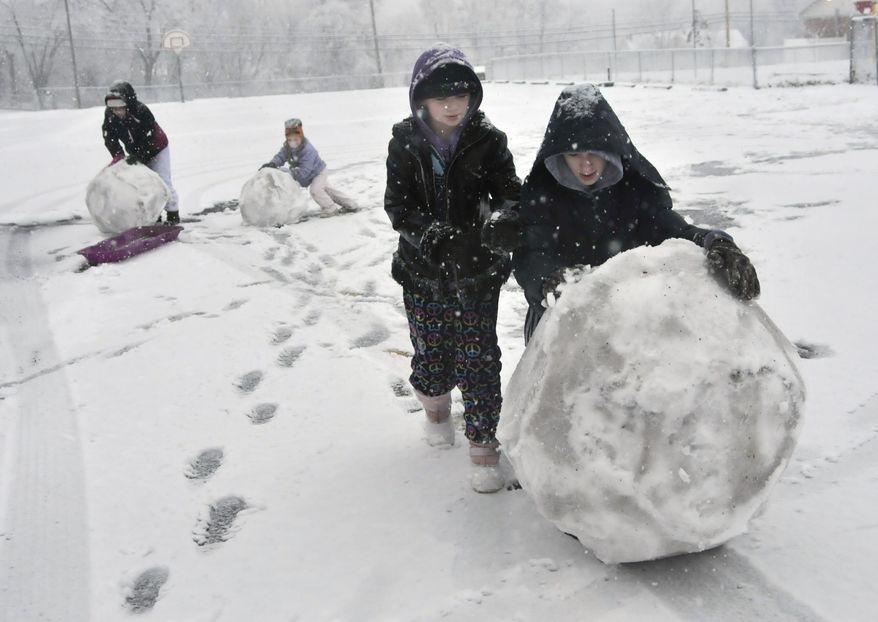 Hailey Greene (from left), 12, Joey Greene, 6, Carly Greene, 10, and Tyler Greene, 14, make a snowman on Monday, Dec. 24, 2012, as a Christmas Eve snowstorm blows through Martinsburg, W.Va. (AP Photo/Journal Newspaper, Ron Agnir)