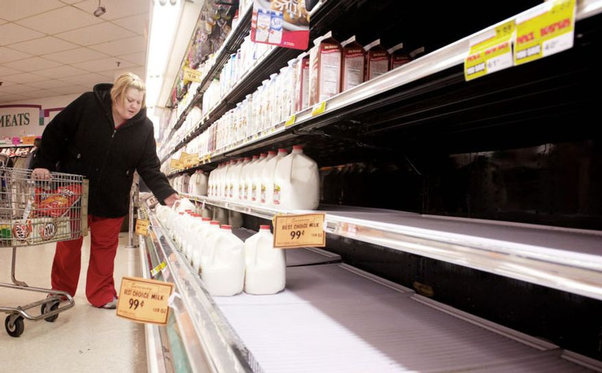 With the store shelves thinning out, Christie Wilson, Sebree, grabs a gallon of milk as shoppers at Sureway Eastgate, in Henderson, stock up before the forecasted blizzard hits late Christmas evening, Tuesday, Dec. 25, 2012. (AP Photo/The Gleaner, Mike Lawrence)