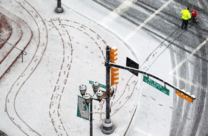 A person salts the sidewalk in downtown Newark, N.J., on Wednesday. Forecasts called for 12 to 18 inches of snow inland from western New York to Maine starting late Wednesday into Thursday, then tapering off into a mix of rain and snow closer to the coast. (Associated Press)