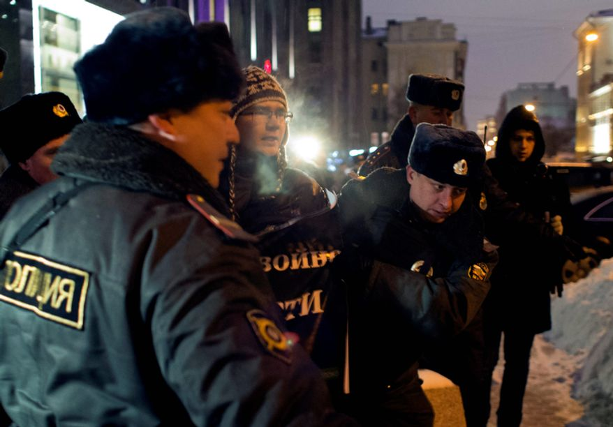 Russian police officers detain a protester outside the Federation Council on Dec. 26, 2012. Several protesters were detained that morning outside the upper chamber of Russia's parliament, which is set to vote on a measure banning Americans from adopting Russian children. (Associated Press)