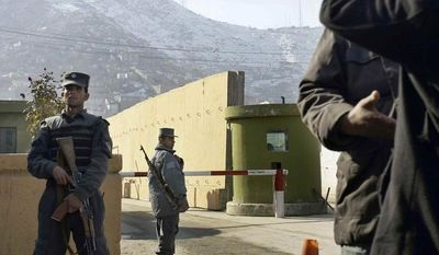 Afghan policemen stand guard outside of Kabul police headquarters, where a an American adviser was killed, in Kabul, Afghanistan, Monday, Dec. 24, 2014. An Afghan policewoman killed an American adviser at the Kabul police headquarters on Monday, a senior Afghan police official said. (AP Photo/Musadeq Sadeq)